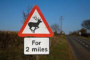 Road sign warns of deer for 2 miles ahead
