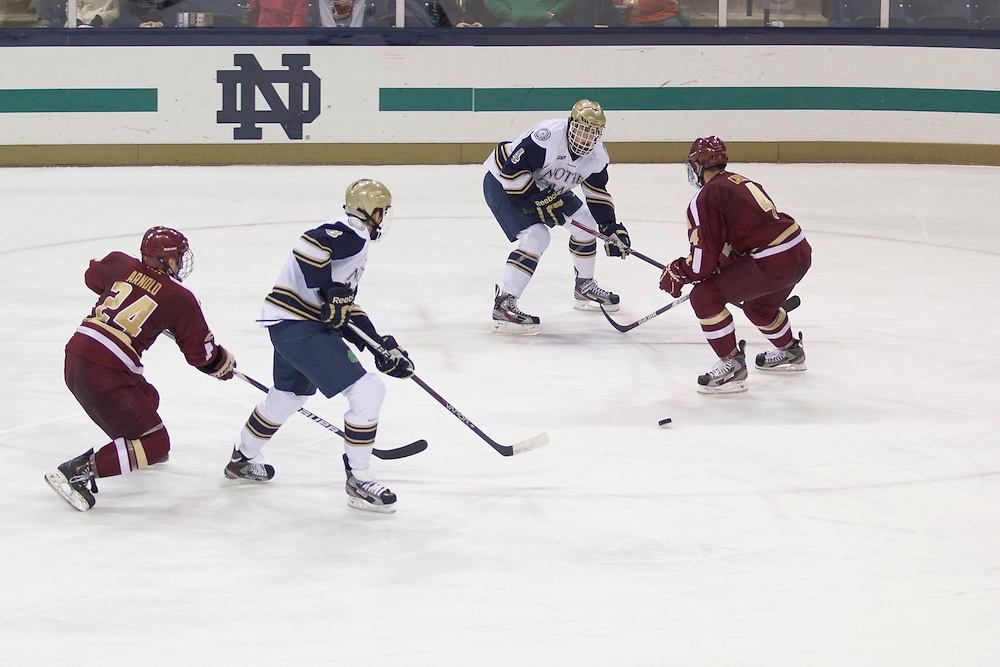Notre Dame center Riley Sheahan (#4) passes the puck to defenseman Shayne Taker (#3) in action during NCAA hockey game between Notre Dame and Boston College.  The Notre Dame Fighting Irish defeated the Boston College Eagles 3-2 in game at the Compton Family Ice Arena in South Bend, Indiana.