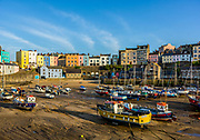 Low Tide at Tenby Wales Harbour along their colorful sea front buildings and boats resting in sand on harbor floor.  Licensing and Limited Edition Prints