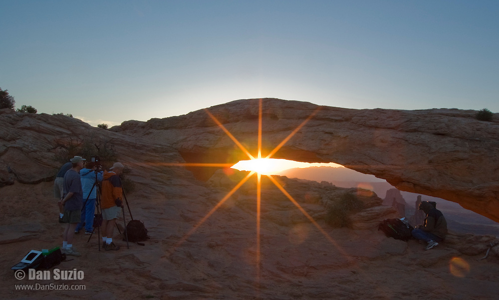Photographers gather to shoot the sunrise through Mesa Arch in Canyonlands National Park, Utah