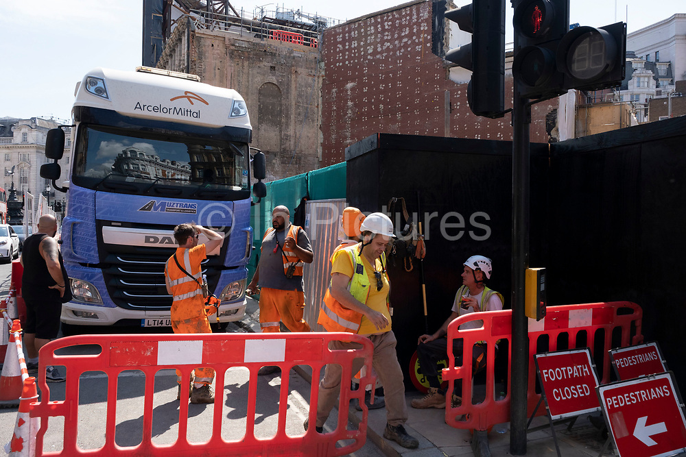 Construction workers at a large site of a whole block due for redevelopment just behind the famous electronic advertising boards at Piccadilly Circus on 26th June 2020 in London, United Kingdom. The site, which is on a massive scale, reveals the inner brickwork of the buildings exposed.