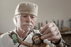 Senior sculptor works on a Jesus Christ statue at workshop, Bavaria, Germany