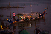 FISHERMEN MEKONG RIVER. South East Asia, Cambodia, Phnom Penh, Mekong River. The Cham fisher people live in various desolated villages along the banks of the Mekong and Tonle Sap rivers. The fisher families live like river gypsy nomads, working and living on their boats, sleeping under a sprung bamboo frame, all their worldly goods stored below deck. They live in extended families, with numerous boats, together for safety. Their diet is rice, vegetables and fish. Their sleek wooden boats are powered by petrol outboard motors with batteries or generators to supply lighting at night. Their fishing technique is laying nets twice or three times per day, which are weighted well below the surface, using old paint aerosal canisters as buoyant floaters, hanging just beneath the surface. These particular fisher families, living at the junction of the Mekong and Tonle Sap rivers, overlooked by Phnom Penh, sell their catch at the Vietnamese market, on the banks of the river. Their life and fortunes are controlled by the cycle of the river. As the river levels drop, so the quantity of fish decreases, until after the heavy floods of the monsoon they fill the river again. They are poor traditional Muslims, marginalised from mainstream society, living a third world life in the immmediate shadow of the first world. The Cham, originally a people of an ancient kingdom called Champa, are a small and disenfranchised community who were disinherited of their land. They are a socially important ethnic group in Cambodia, numbering close to 300,000. The Cham people, live in some 400 villages across Kampong Chnang and Kampong Cham provinces. Their religion is Muslim and their language belongs to the Malayo-Polynesian family. Their livelihoods are as diverse as rice farming, cattle trading, hunting and fishing.///A Cham woman steering her fishing boat at dusk on the Mekong river