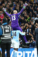 Manchester City Goalkeeper Wilfredo Caballero is lifted by Wilfried Bony of Manchester City as they celebrate the win. Capital One Cup Final, Liverpool v Manchester City at Wembley stadium in London, England on Sunday 28th Feb 2016. pic by Chris Stading, Andrew Orchard sports photography.