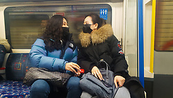 © Licensed to London News Pictures. 28/02/2020. London, UK. Women wearing fashionable face masks as a precaution against new type coronavirus (COVID-19) are seen on a London Underground train. Two more people have tested positive for coronavirus in England, bringing the total number of UK cases to 15. Photo credit: Dinendra Haria/LNP