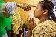 04 JUNE 2014 - YANGON, YANGON REGION, MYANMAR: A woman touches her forehead to a deity for good luck in Botataung Paya (Pagoda) in Yangon, Myanmar (Rangoon, Burma). Botataung is one of the most famous pagodas in Yangon with maze like interior of gold leaf covered walls. The pagoda houses a hair from the Buddha and is one of the most sacred sites in Burma. Yangon, with a population of over five million, continues to be the country's largest city and the most important commercial center.     PHOTO BY JACK KURTZ