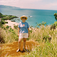 1. When was this photo taken?<br /> <br /> Summer 2000<br /> <br /> 2. Where was this photo taken?<br /> <br /> Oahu, Hawaii<br /> <br /> 3. Who took this photo?<br /> <br /> Mary Keane<br /> <br /> 4. What are we looking at here?<br /> <br /> I am near the Pupukea Heiau above Waimea Valley<br /> <br /> 5. How does this old photo make you feel?<br /> <br /> Happy to be enjoying very special sightseeing in Hawaii with family who live there. So many places that we saw were unique and off the beaten path giving a true taste of local life.<br /> <br /> 6. Is this what you expected to see?<br /> <br /> I expected to see black and white photos from the sixties<br /> <br /> 7. What kind of memories does this photo bring back?<br /> <br /> Wonderful memories of many visits over the years to family in Hawaii. It is always special to spend extended time visiting family where days are spent enjoying each others company<br /> <br /> 8. How do you think others will respond to this photo?<br /> <br /> They may plan a trip to Hawaii