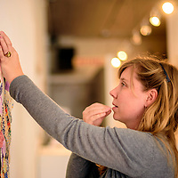 041015  Adron Gardner/Independent<br /> <br /> Kristi Wilson pulls a pin from her teeth to tack an exhibit piece to a wall at Art123 in Gallup Friday.