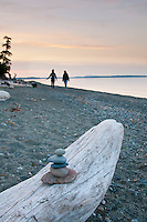 Sunset glows pink as two girls walk with a dog along the beach at Cordova Bay, Victoria, BC.