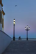 Cyclist at dawn in Cadiz, Spain