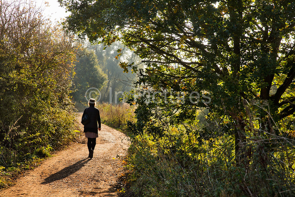 A woman walks along a country path near the River Stour at Flatford in East Bergholt, on 29th October 2016 in Suffolk, England. John Constable the painter was born here and is known principally for his landscape paintings of Dedham Vale, the area surrounding his home—now known as Constable Country.