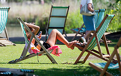 © Licensed to London News Pictures. 10/06/2014. London, UK. A woman relaxes in Hyde Park.  Londoners enjoy the sunny weather today 10th June 2014. Photo credit : Stephen Simpson/LNP