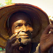 The smile that lurks beneath the pointed hat. Similar to the hat of choice of Vietnam's farmers, this model is similarly excellent for shielding the wearer from harsh sunlight while working. Kolda, Senegal.