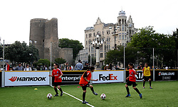 Local kids play football infant of the Maiden Tower in Baku, Azerbaijan.