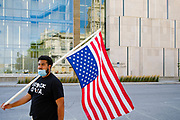 23 JULY 2020 - DES MOINES, IOWA:  JAYLEN CAVIL, a member of Black Lives Matter, carries an upside down American flag in front of the Polk County Criminal Court. About 75 members of Des Moines Black Lives Matter protested in support of Viet Tran, one of their members who was arrested by Des Moines Police on July 1. He was arrested on charges of disseminating classified or confidential police information because during an interview with a local TV station, he held a memo from the Des Moines Police Department naming individuals police wanted to arrest on vandalism charges. He got the memo from another Black Lives Matter protester. During today's bond hearing the court ruled that Tran should be released and subjected to electronic monitoring before the weekend.        PHOTO BY JACK KURTZ