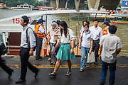 21 NOVEMBER 2012 - BANGKOK, THAILAND:  Passengers disembark a Chao Phraya Express boat at Sathorn Pier in Bangkok. The Chao Phraya Express boats run up and down the Chao Phraya River in Bangkok providing a sort of bus service for neighborhoods near the river. The boats are the fastest way to get from north to south in Bangkok. Thousands of people commute to work daily on the Chao Phraya Express Boats and fast boats that ply Khlong Saen Saeb. Boats are used to haul commodities through the city to deep water ports for export.   PHOTO BY JACK KURTZ