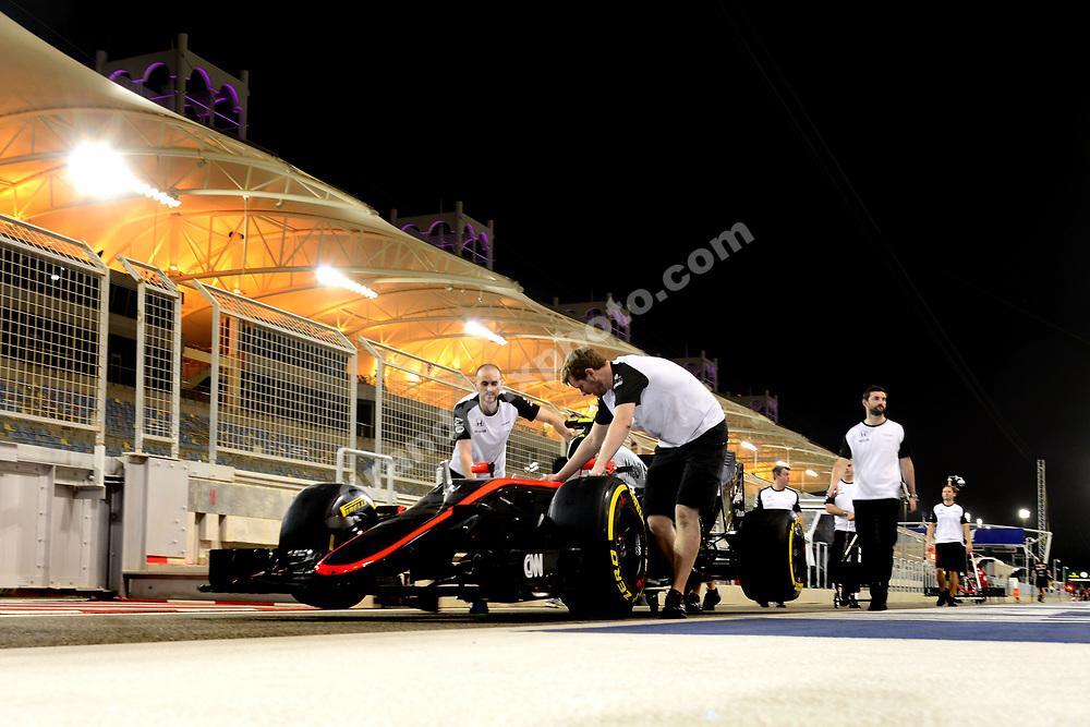 McLaren-Honda mechanics push the car of Jenson Button in rhew pit-lanen at night before the 2015 Bahrain Grand Prix. Photo: Grand Prix Photo