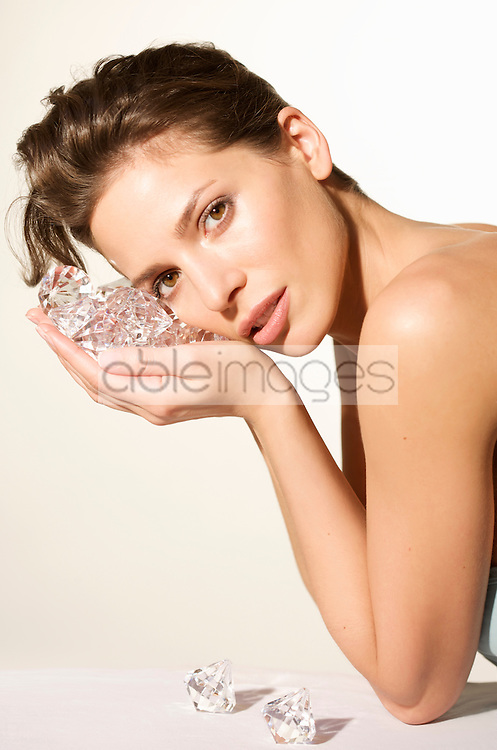 Young woman holding large diamonds next to her face