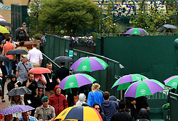 Spectators shelter under umbrellas as rain falls on day eight of the Wimbledon Championships at The All England Lawn Tennis and Croquet Club, Wimbledon.