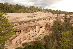 North America, United States, Colorado, Mesa Verde National Park, tourists exploring Cliff Palace, an ancient cliff dwelling.  Mesa Verde was home to the Ancestral Pueblo people from approximately 600 A.D. to 1300 A. D. Mesa Verde is Spanish for 'green table.'