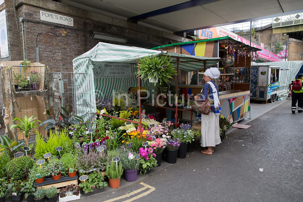 A lady wearing a white headscarf shops in Brixton Marker on Popes Road on 23rd July 2017 in South London, United Kingodm