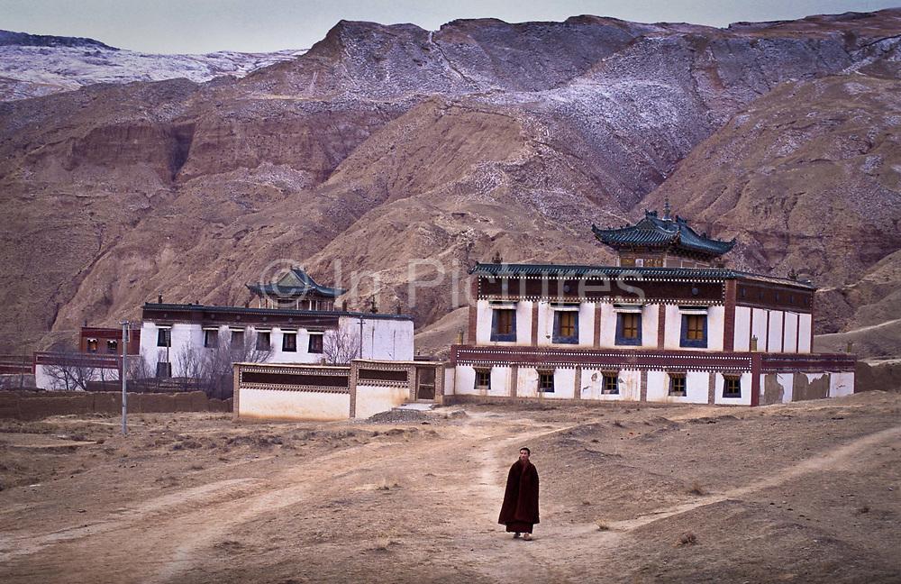 Tibetan buddhist monk Dongyu, walks through the grounds of 300 years old Atsog Monastery, Xinghai County, Qinghai Province, China