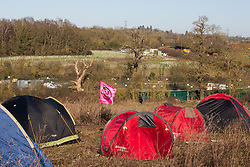 Harefield, UK. 19 January, 2020. A camp pitched by activists from Extinction Rebellion, Stop HS2 and Save the Colne Valley attending a 'Stand for the Trees' event timed to coincide with tree felling work for the high-speed rail link on land from which bailiffs acting for HS2 had evicted activists living in the Colne Valley wildlife protection camp almost two weeks previously. 108 ancient woodlands are set to be destroyed by the high-speed rail link. Examples of saplings planted as mitigation measures by HS2 appear in the distance.
