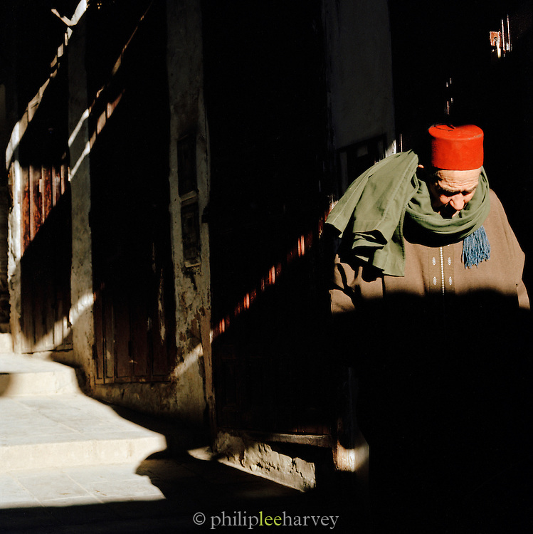 A man in a fez hat walks through the shadowy, narrow streets of Fes in Morocco