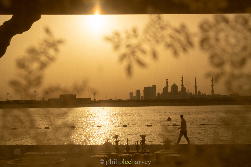 Silhouette of a man walking along a beach at the Shangri La Hotel with the view of Sheikh Zayed Mosque in the background under an orange sky at sunset, Abu Dhabi, United Arab Emirates