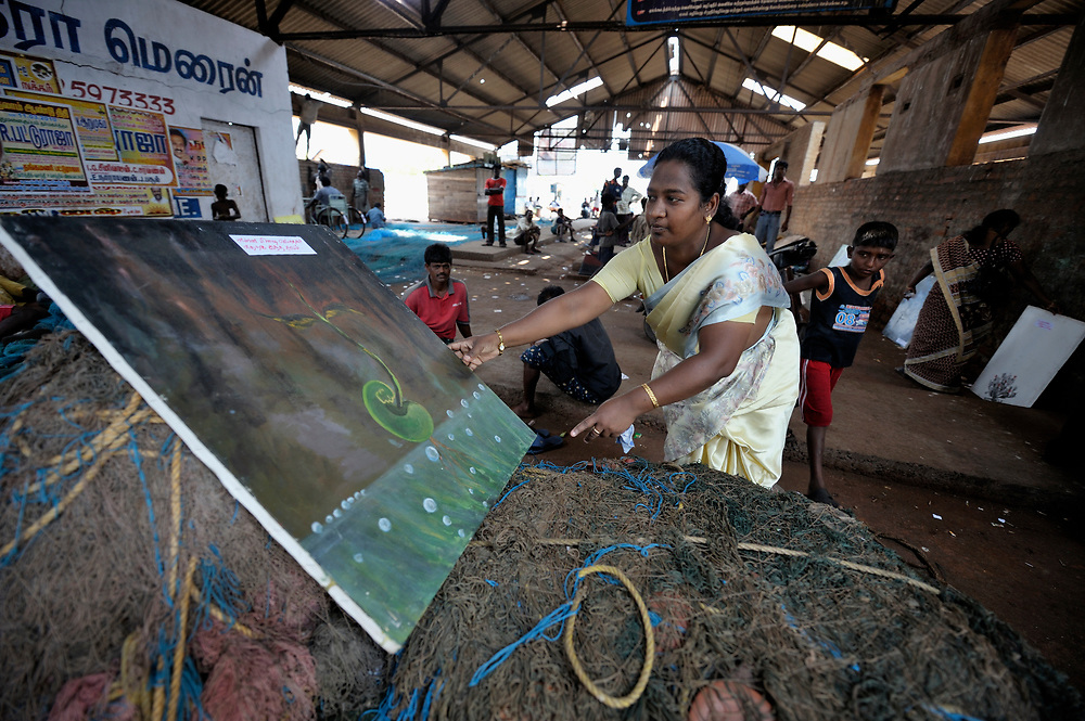Glory Premlatha, an educator with the Madras Christian Council of Social Service, sets out artwork on a pile of fishing nets as part of an educational campaign directed toward fishers in the port of Chennai, India, explaining HIV and AIDS and how HIV can be transmitted.