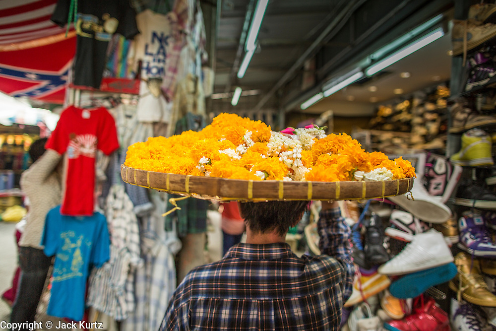 16 FEBRUARY 2013 - BANGKOK, THAILAND:   A flower garland seller walks through the Chatuchak Weekend Market in Bangkok. Chatuchak Weekend Market in Bangkok is reportedly the largest market in Thailand and the world's largest weekend market. Frequently called J.J., it covers more than 35 acres and contains upwards of 5,000 stalls.    PHOTO BY JACK KURTZ