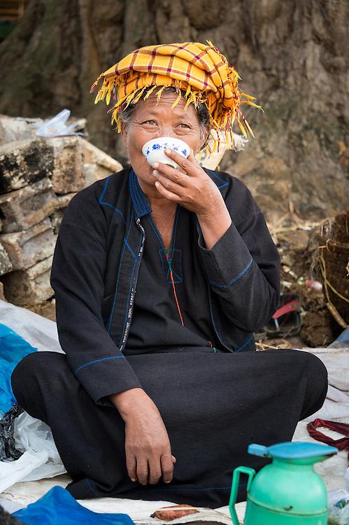 INLE LAKE, MYANMAR - CIRCA DECEMBER 2013: Burmese woman drinking tea in the Taung Tho Market in Inle Lake, Myanmar
