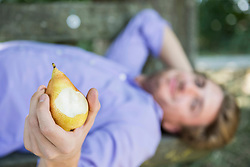 Mid adult man lying on bench and eating pear