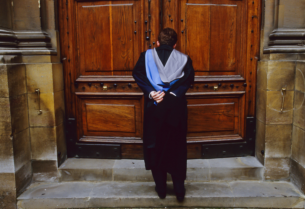A man waits at the doors of Oxford University for graduation.