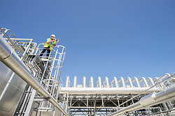 Low angle view of an engineer using a megaphone at geothermal power station, Bavaria, Germany