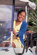 Photographie en couleur d'une jeune femme Kanak souriante au volant d'un club Car de l'hôtel 5* Le Méridien Ile des Pins en Nouvelle Calédonie.