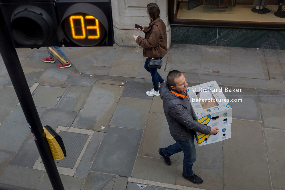 A delivery man carries a box of ordered bananas, on 28th October 2019, in Westminster, London, England.