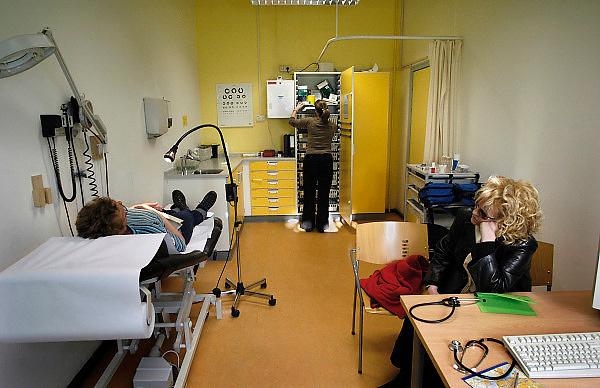 Nederland, Nijmegen, 11-7-2005..Een arts, huisarts, van de huisartsenpost, huisartsendienst, pakt verbandmiddelen uit een kast in de spreekkamer. Avonddienst, bereikbaarheid, spoedgeval, ongelukje. Gezondheidszorg, eerstelijns zorg. Zorgverzekeraar, zorgverzekering. Basispakket. Basisverzekering...Foto: Flip Franssen