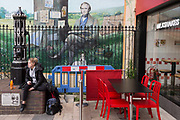 A young woman rests in front of a section of the Darwin mural located in front of a snack and milkshake bar in the pedestrianised area of Bromley town centre, on 3rd February 2020, in Bromley, London, England. Victorian evolutionist Charles Darwin lived in nearby Downe in Kent and his mural dates from 2009.  .