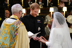 Prince Harry places the wedding ring on the finger of Meghan Markle in St George's Chapel at Windsor Castle during their wedding service, conducted by the Archbishop of Canterbury Justin Welby.