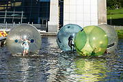 Children play inside Waterwalkerz, human hamster balls under the Falkirk Wheel, in central Scotland, United Kingdom, Europe. Built in 2002, the Falkirk Wheel reconnects the Forth and Clyde Canal with the Union Canal for the first time since the 1930s.