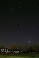 Middletown, New York - The planets Jupiter, top left, Venus, center, and the crescent moon form a diagonal line in the twilight sky on Feb. 23, 2012. The lights of a passing plane are visible above Jupiter.