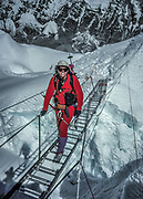 New Zealand mountaineer Gary Ball crosses a ladder over a large crevasse in Khumbu icefall, during climb of Chomolungma, Mt Everest, Nepal, Himalaya
