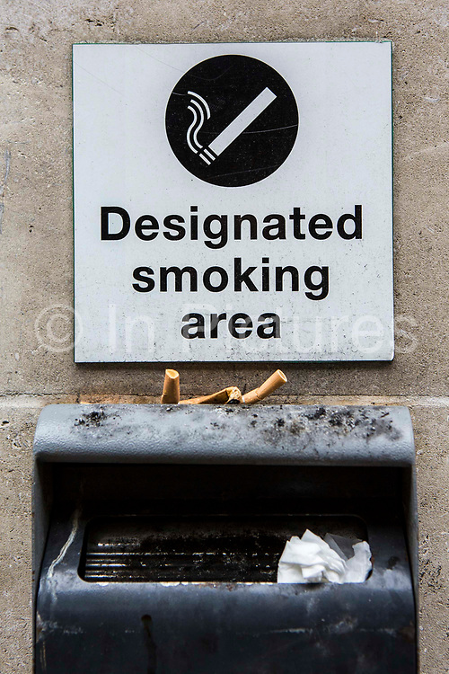 Designated smoking area sign and ash tray. Outside an office building.  London. UK.