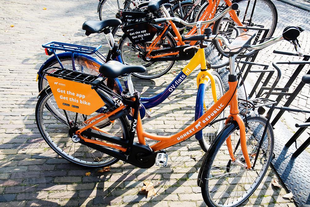 In Utrecht staan huurfietsen van het Deense fietsverhuurbedrijf Donkey Republic naast de OV-fiets. De deelfietsen van Donkey Republic kunnen met een app worden gehuurd en worden ontgrendeld met bluetooth. In tegenstelling tot de Obike moeten de fietsen naar een vaste fietsenstalling worden gebracht. Zo moet de overlast beperkt worden.<br /> <br /> In Utrecht rental bikes from the Danish bicycle rental company Donkey Republic are parked in the city center. The sharing keys can be rented with an app and unlocked with bluetooth. Unlike Obike, the bikes must be brought to a fixed bicycle storage room. Thus, the nuisance must be limited.