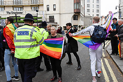 © Licensed to London News Pictures. 06/04/2019. LONDON, UK.  A member of the LGBT community argues with the police during a protest outside the Brunei-owned Dorchester Hotel in reaction to reports that the Sultan of Brunei decreed that adultery and gay sex is punishable by death by stoning in the Islamic sultanate.  Several large clients of the Dorchester Hotel have already ceased bookings in response to the decree.  Photo credit: Stephen Chung/LNP