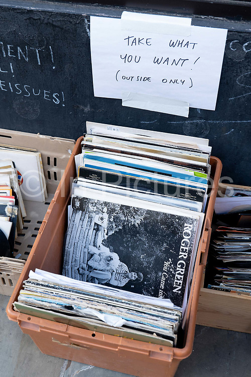 Free records outside an East London record shop on Bethnal Green Road with a sign saying Take What You Want - Outside Only on the 5th September in East London in the United Kingdom.
