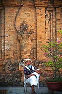 A Vietnamese man sits on a chair in Po Nagar cham temple, Nha Trang, Vietnam, Southeast Asia