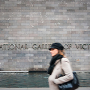 Woman walking past facade of National Gallery of Victoria