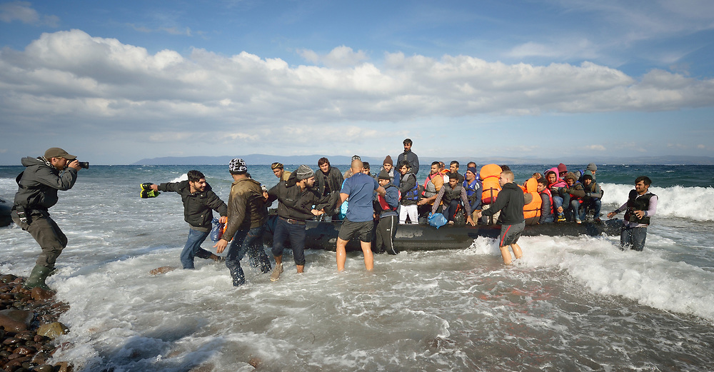 Refugees land on a beach near Molyvos, on the Greek island of Lesbos, on October 31, 2015. They arrived in the boat from Turkey, for which they paid traffickers huge sums. They were received in Greece by local and international volunteers, then proceeded on their way toward western Europe.
